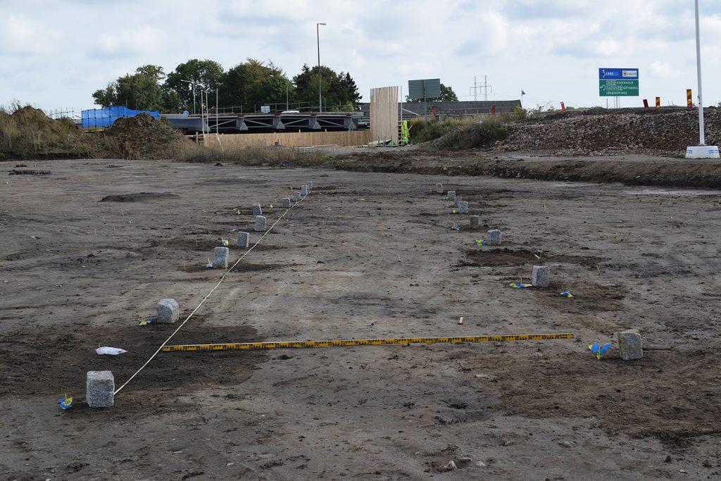 Lämningarna efter ett av långhusen från mellersta-yngre bronsålder, ca 1200-700 f. Kr sett från väster. Stolphålen som stolparna i den takbärande konstruktionen stått i har markerats med gatstenar. I bakgrunden ser man brobygget över E6:an.