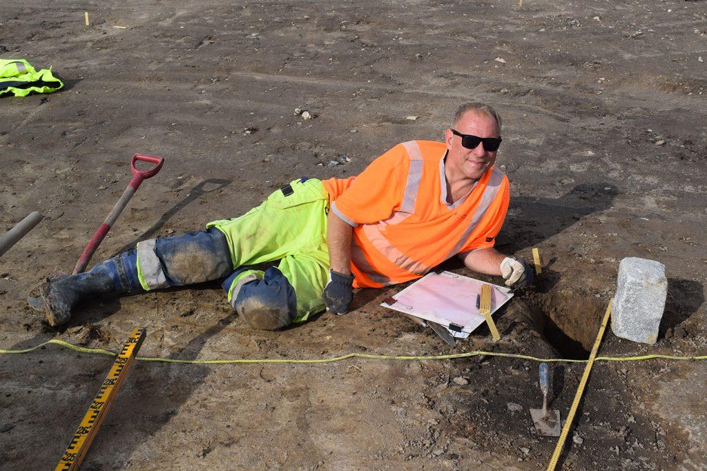 Håkan Aspeborg undersöker och dokumenterar ett stolphål i ett av långhusen.