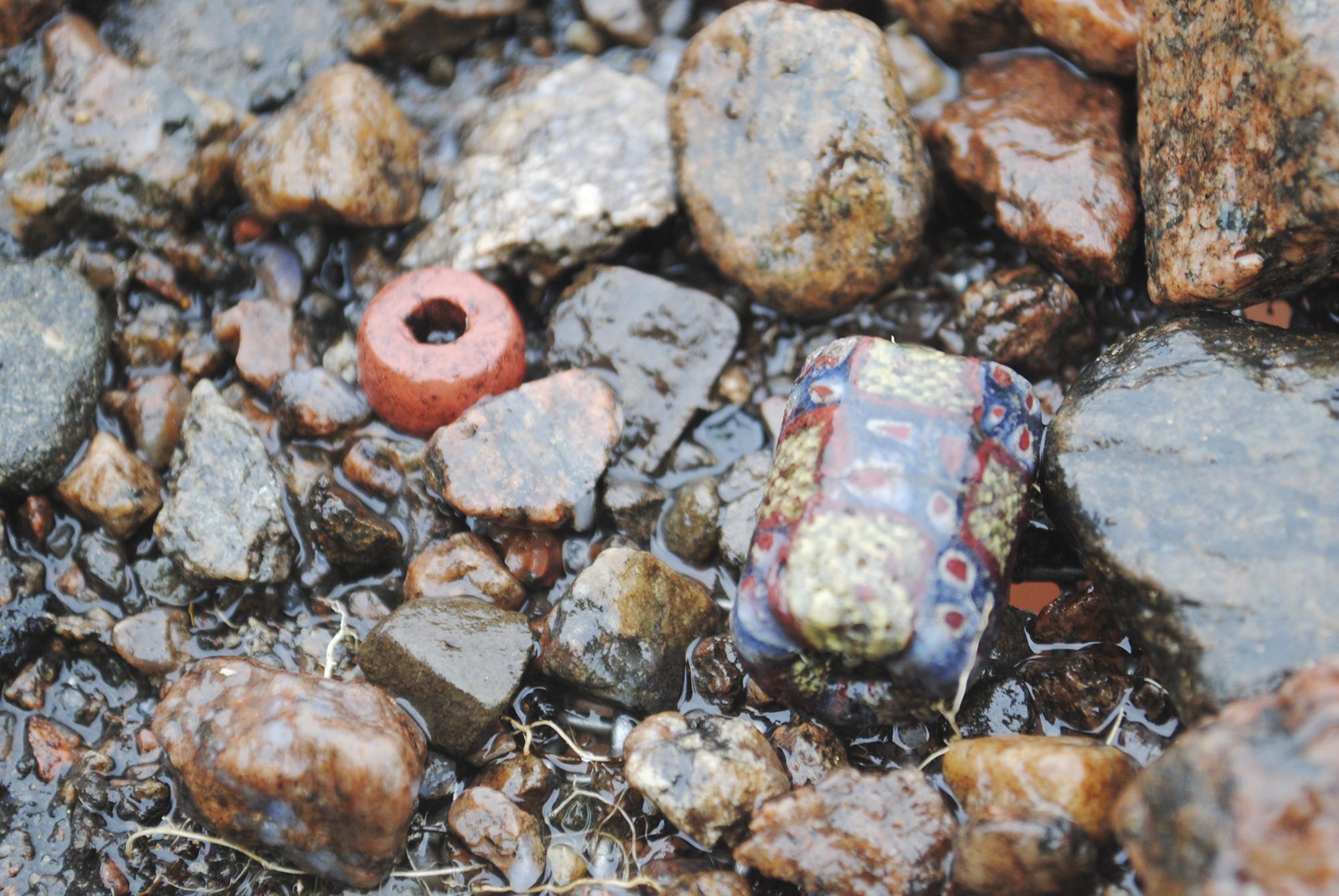 Två glaspärlor i sållet. Foto: Elin Säll, Arkeologerna.