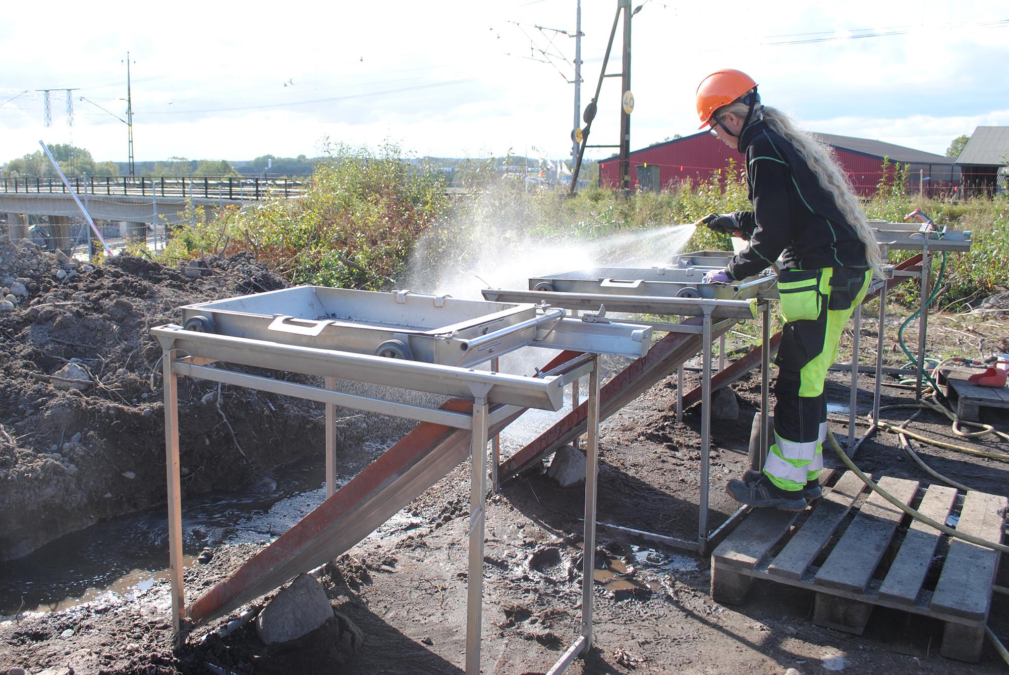 Sigrid sållar jord från ett brandlager. Foto: Elin Säll, Arkeologerna.
