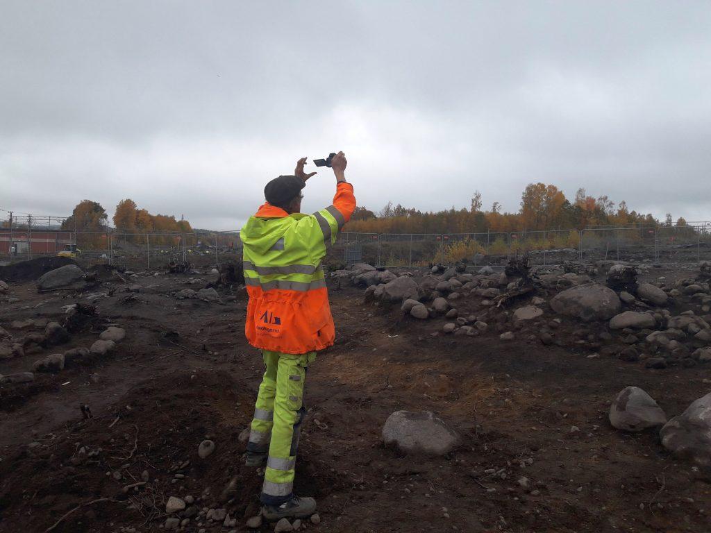 En arkeolog håller kameran högt över en gravhög