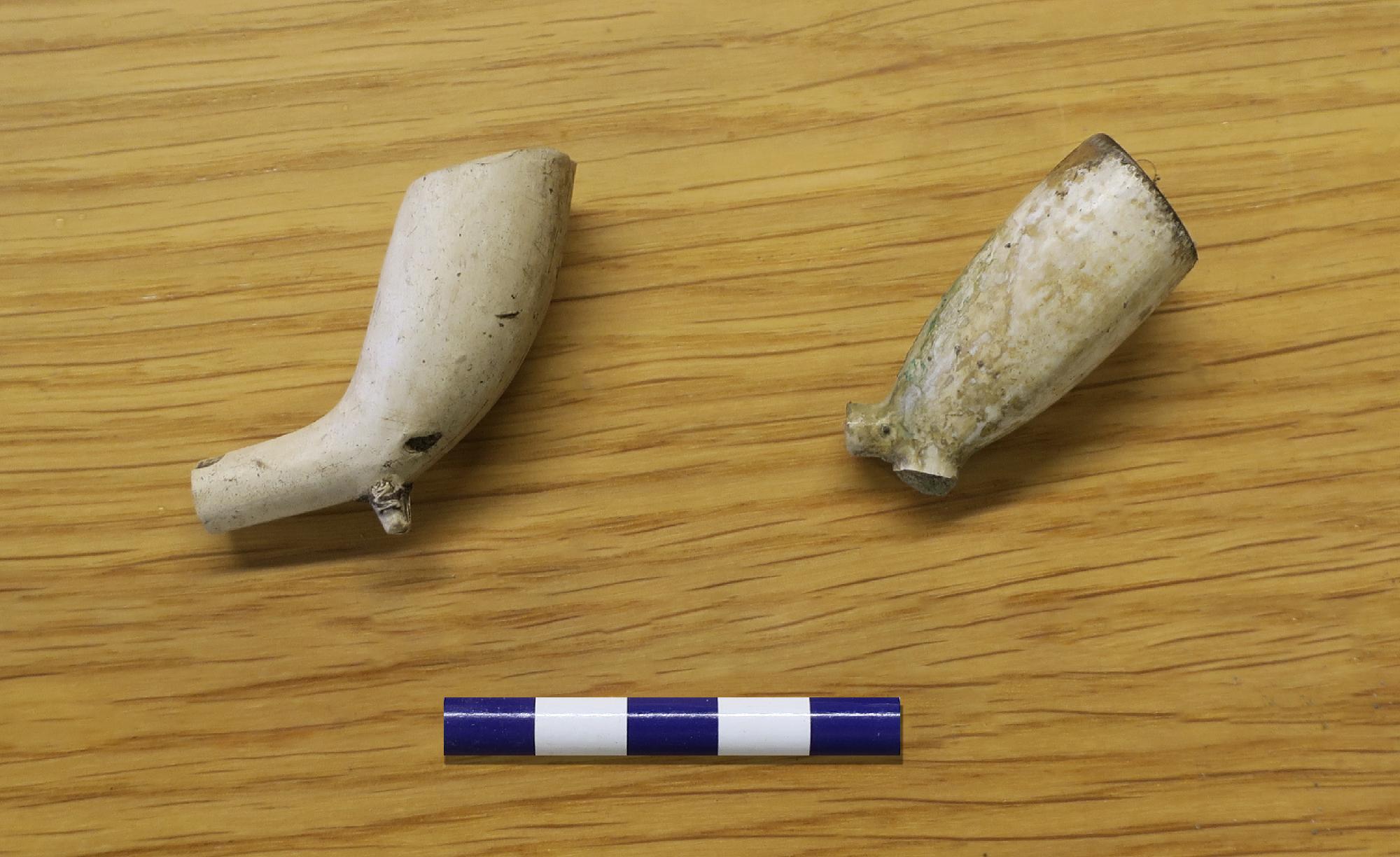 Pipan till höger är en holländsk pipa, tillverkad i Gouda med en datering till ca 1720–1739. Till vänster en engelsk pipa, tillverkad i London av William Manby från 1719 och framåt (muntlig uppgift Bergman-Carter, R). Foto: Arkeologerna.