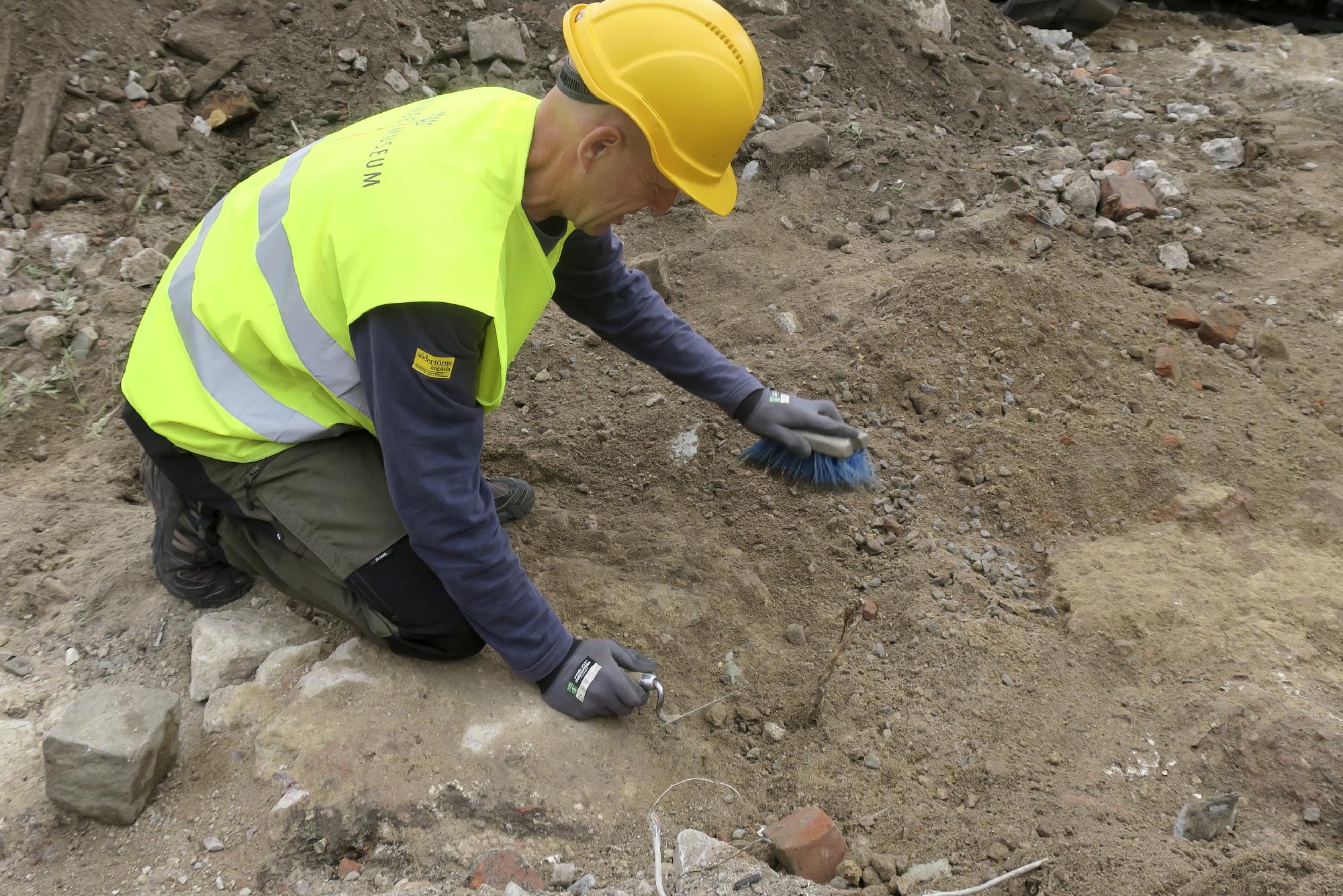 Mikel Björk från Blekinge museum rensar fram grunden till ett stort hus. Foto: Arkeologerna.