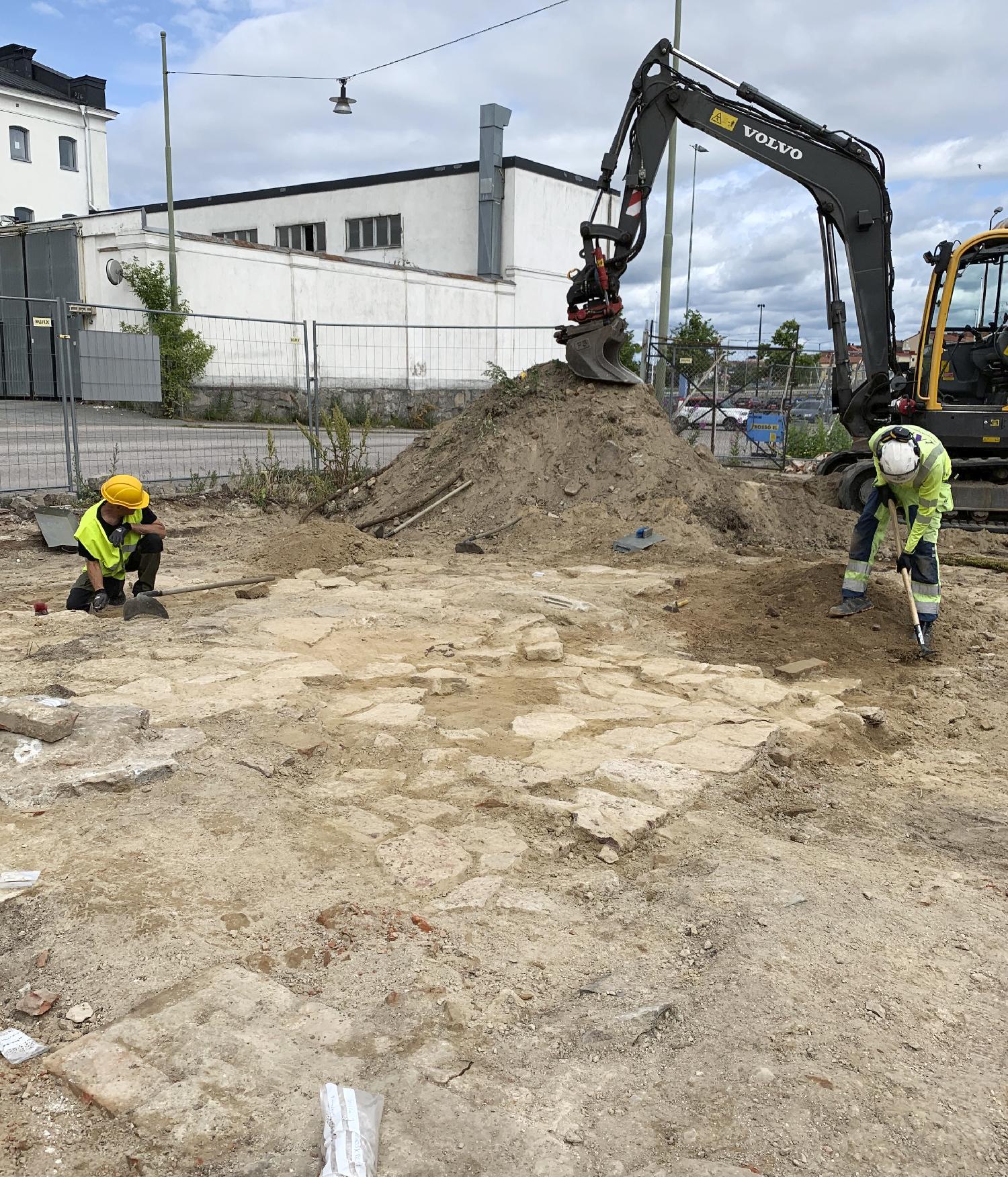 Arkeologerna Mikael Björk och Albin Norqvist rensar fram kritpipsugnen. Foto: Lotta Stenqvist, Arkeologerna.