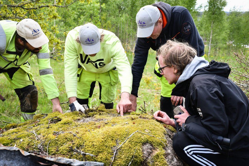 Johannes (utan keps) visar skålgroparna för oss. Foto Krister Kám Tayanin, Arkeologerna.