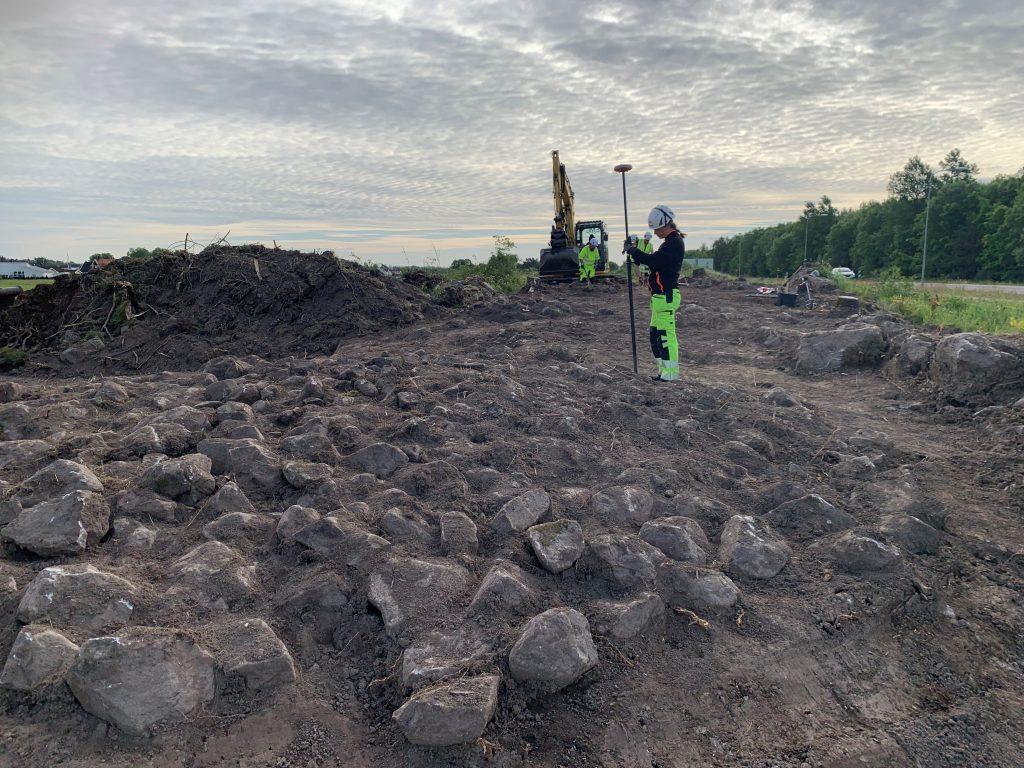 En arkeolog mäter in områdets största stensättning (grav). I bakgrunden fortgår schaktningsarbetet.