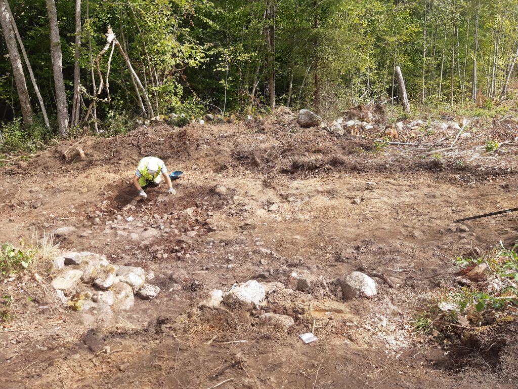 En arkeolog handrensar en stor stenläggning som låg inne i husgrunden