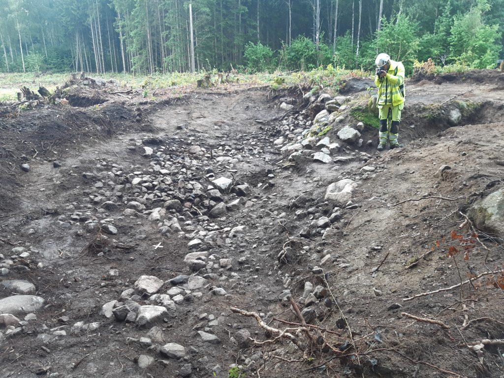 En arkeolog arbetar i fält, till höger syns spisröset.