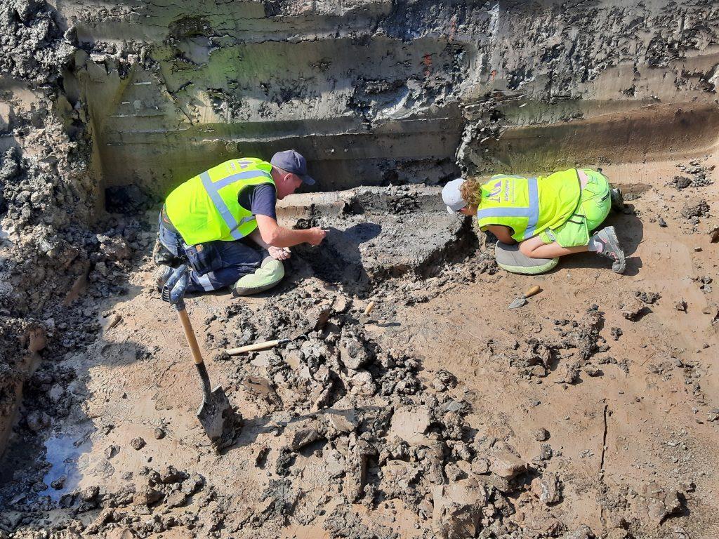 Två arkeologer gräver ut en brunn.