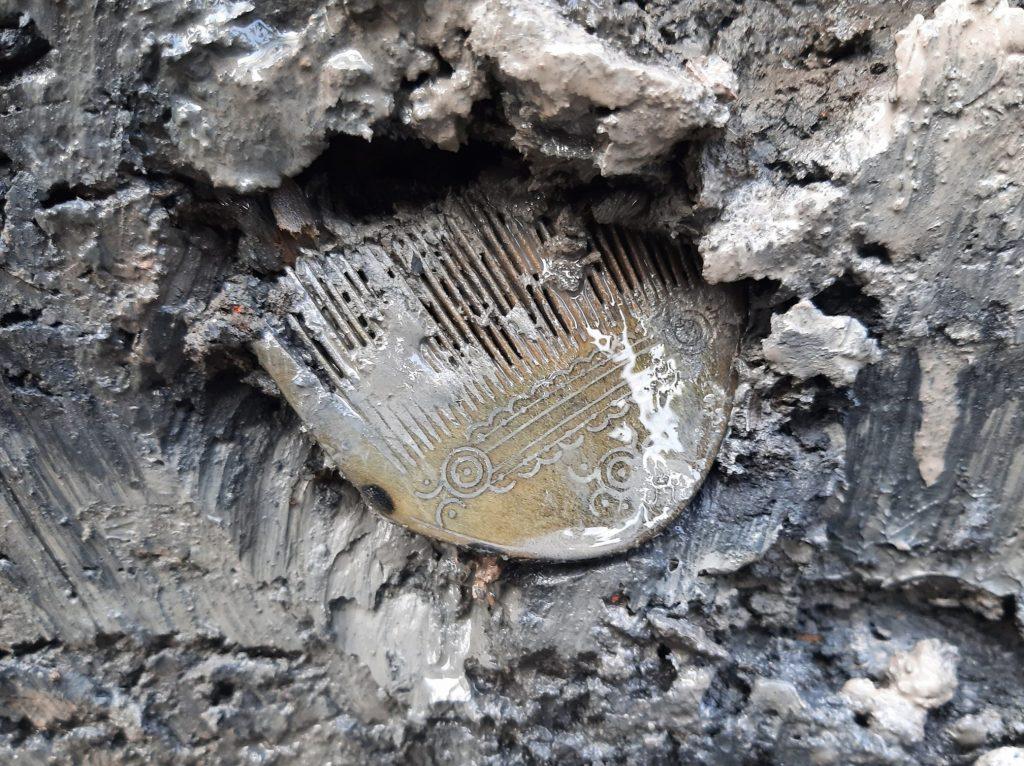 En dekorerad kam som ligger i lera.