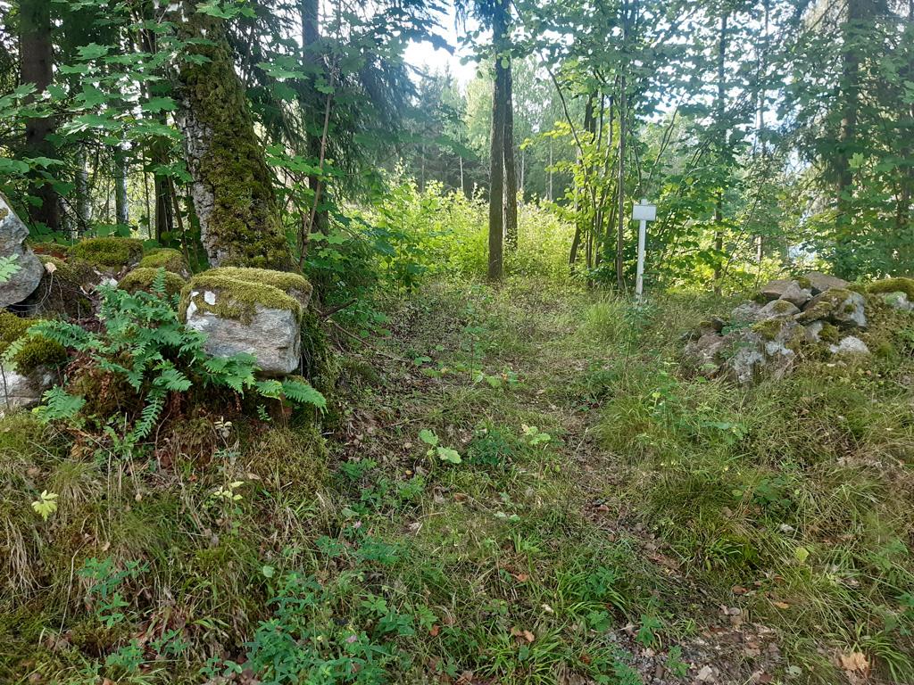 En liten skylt vid en öppning i en stengärdsgård. Bakom muren syns lövsly i en glänta.