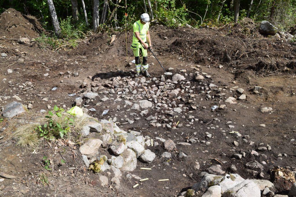 En varselklädd arkeolog undersöker en stenlagd yta med metalldetektor