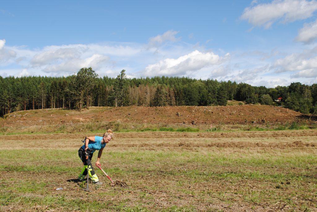 Katarina Österström söker av området vid vägen med metalldetektor.