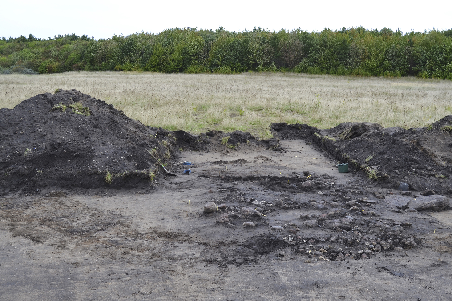 Figur 5. Grav 5. Den rektangulära stenpackningen (långdösen) i gravhögen. Gravrännan skymtar i förgrunden och till vänster i bild. Foto: Magnus Andersson, Arkeologerna. CC-BY.